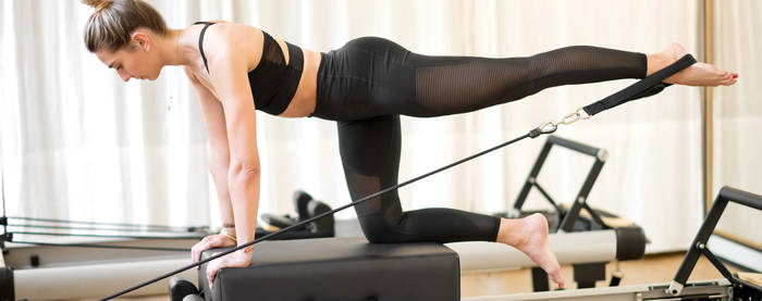 -woman-doing-diagonal-stabilization-pilates-on-reformer