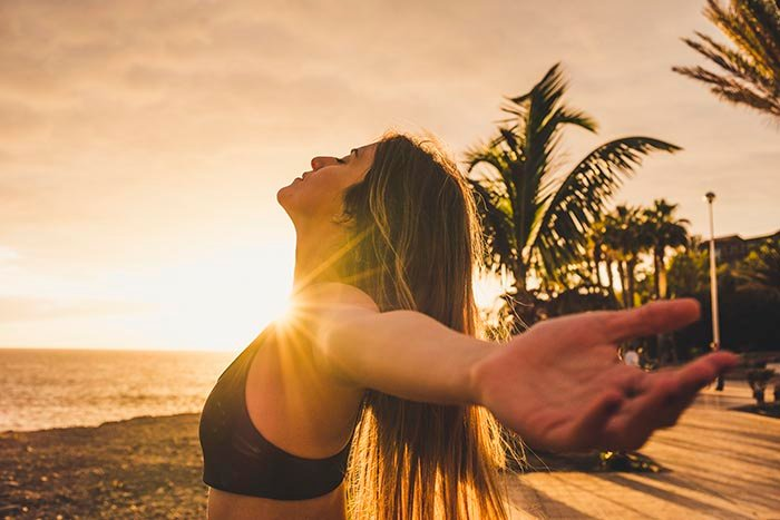 athlete sporty young woman stretching and performing breathing exercises at the beach