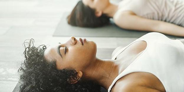 yogis lying in savasana practicing yoga nidra
