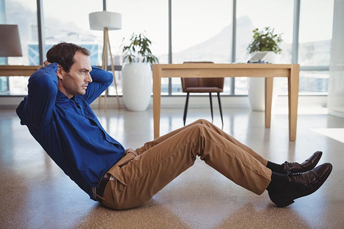 determined-executive-preforming-crunches-as-part-of-workplace-wellness-700