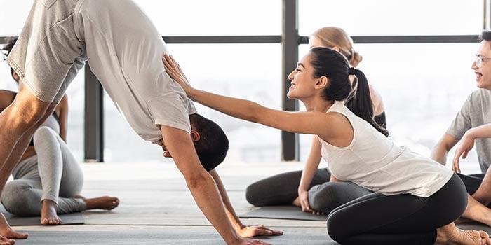 female-coach-correcting-yoga-beginner-at-group-cla-2021-04-05-00-52-55-utc