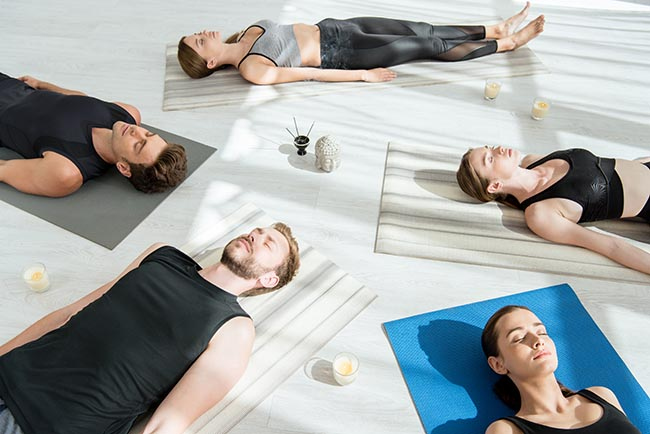 five young individuals meditating in corpse pose experiencing yoga nidra