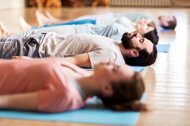 groupe de personnes faisant des exercices de yoga au studio pratiquant le yoga nidra pour les débutants