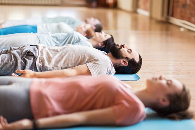 group of people doing yoga exercises at studio practicing yoga nidra for beginners