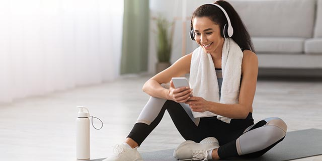 happy-young-woman-resting-on-yoga-mat-listening-to-music