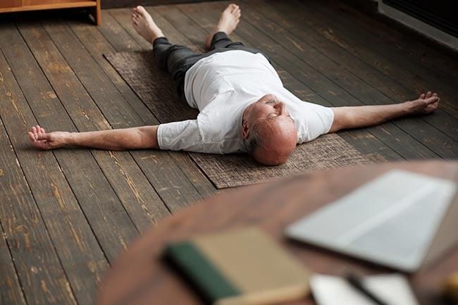man meditating on a wooden floor experiencing the yoga nidra benefits