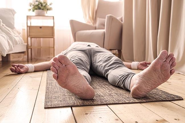man meditating on a wooden floor practicing yoga nidra