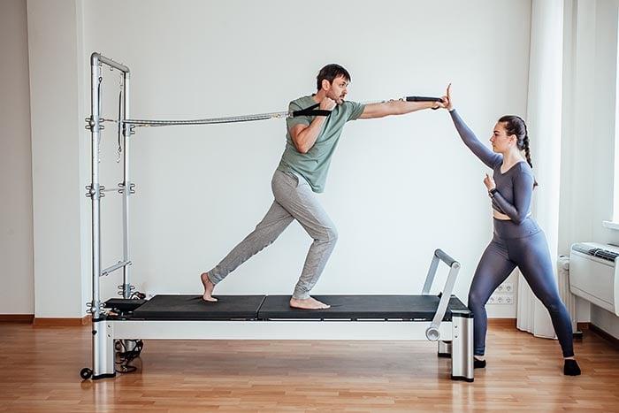 homem fazendo exercícios no reformador de pilates
