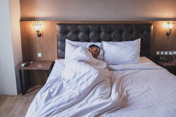 man getting the sleep he needs on his bed