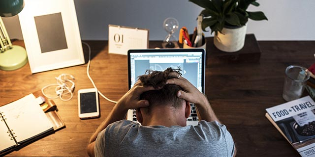 man-stressed-while-working-on-laptop