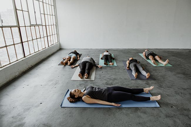 people exercising performing yoga nidra