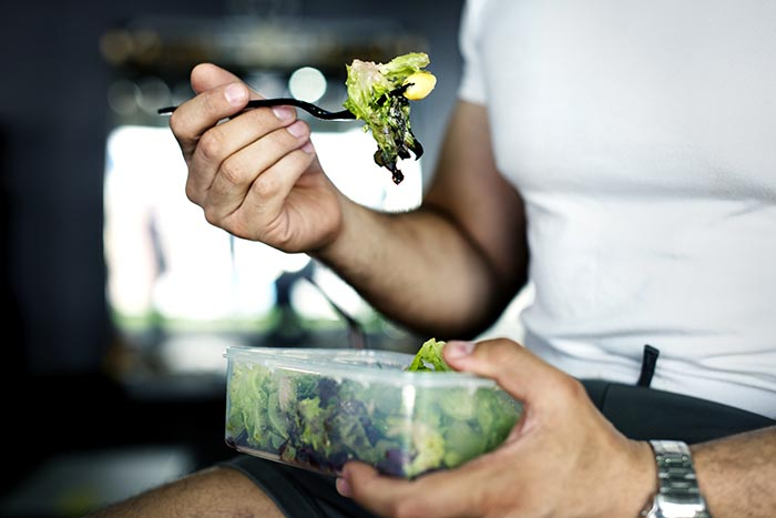 person enjoying mindful eating while eating a salad