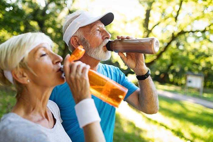Casal sênior ficar hidratado após o exercício
