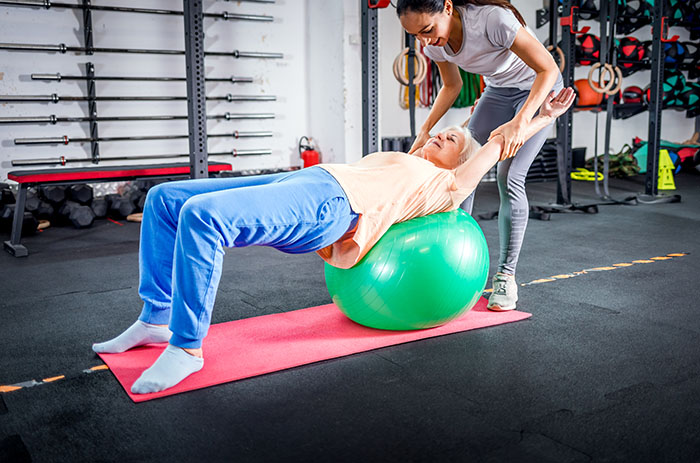 senior woman with trainer doing rehab using pilate for beginners
