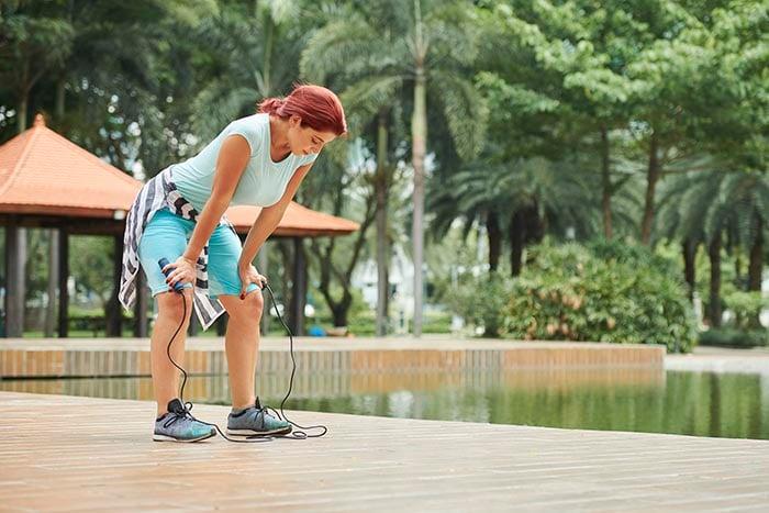 mulher desportiva respirando pesadamente tentando restaurar os níveis de oxigênio