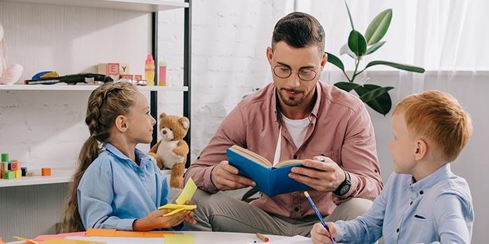 teacher-in-eyeglasses-reading-book-to-kids-at-tabl