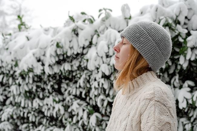 Mulher jovem respira ar fresco e gelado ao ar livre