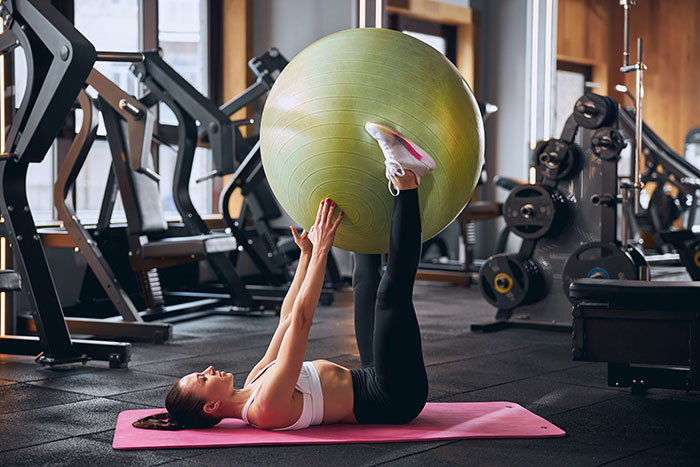 woman doing pilates in gym as part of rehab training