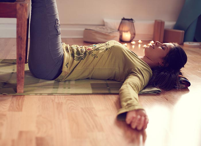 woman doing restorative yoga pose laying on the floor with legs on chair