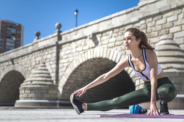 woman doing yoga and pilateso utdoor with her mat as part of yoga for runners
