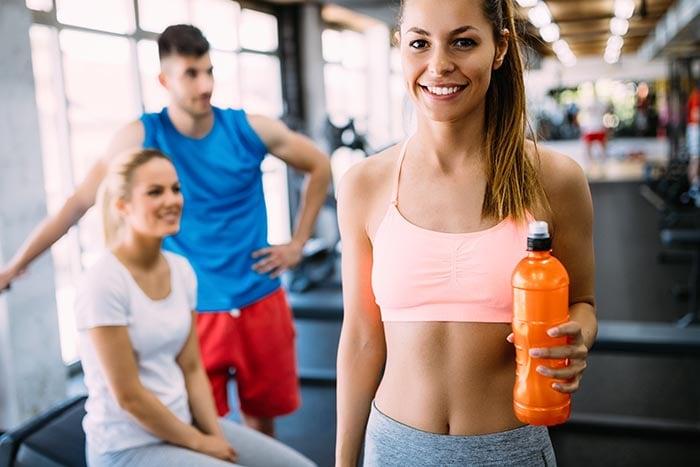 Mulher hidratando durante o exercício beber bebida esporte contendo eletrólitos