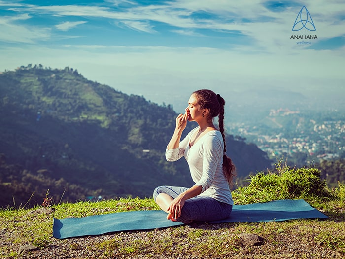 woman practices alternate nostril breathing in lotus pose outdoors