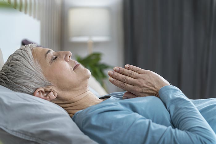 woman practicing guided meditation for sleep laying in bed