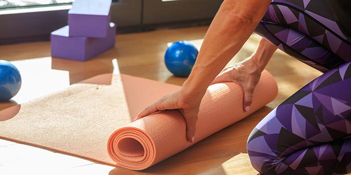 woman-rolling-a-yoga-mat-on-wooden-floor-P5Y8XZF
