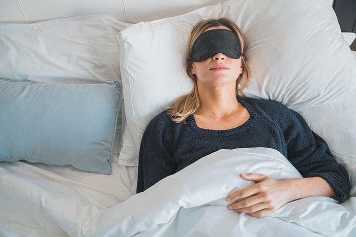 woman sleeping with sleeping mask over her eyes