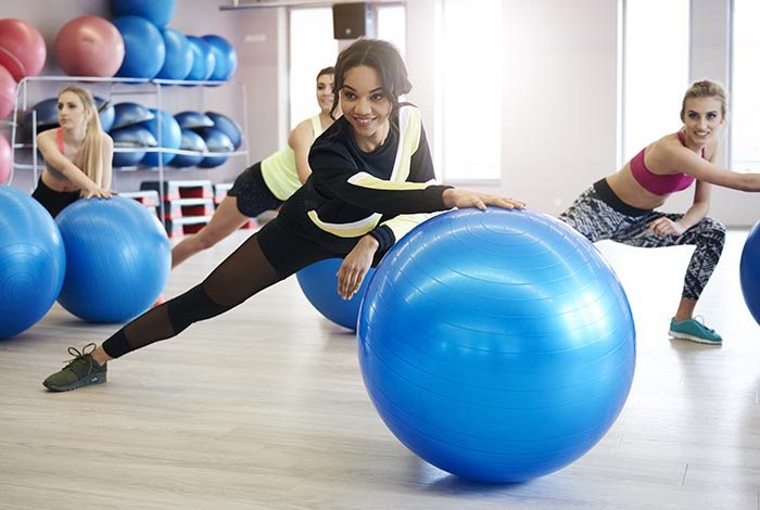 women exercising with fitness and pilates ball and other equipment