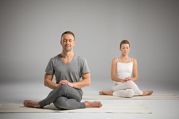 young athletic man and woman sitting in and performing kundalini yoga
