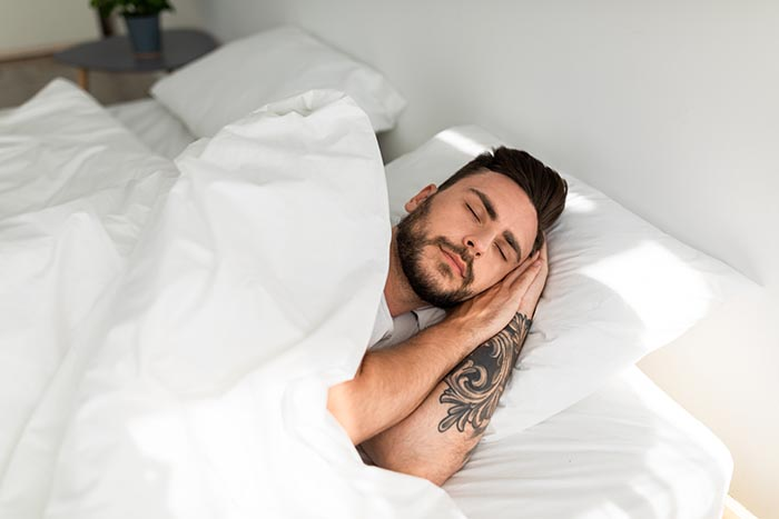 young man in deep sleep after guided meditation for sleep