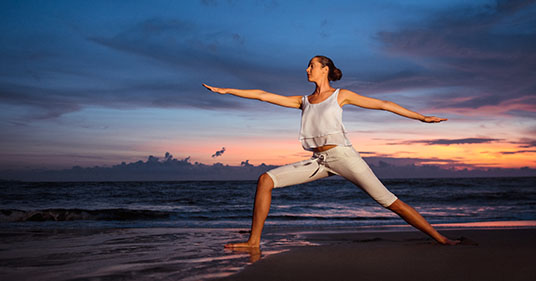 woman performing gentle yoga sequence on the beach to help her reduce stress and pain
