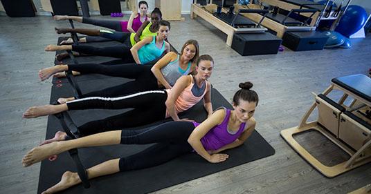 groupe de femme faisant des exercices avec un anneau de pilates, apprenant ce que c'est le pilates et comment le il est pratiqué.