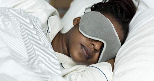 Woman sleeping using a eye mask, to not have her sleep disturbed by the light