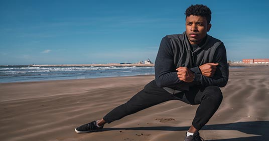athletic man stretching legs before exercise as part of yoga for runners