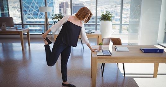 fille debout devant un bureau s'étirant pour participer à un programme de bien-être au travail