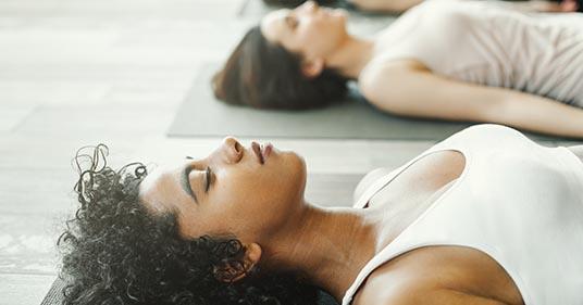 beautiful yogi lying in savasana while doing yoga nidra