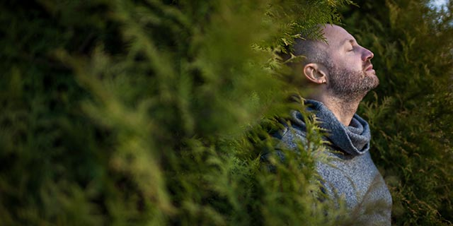man breathing exercise breathe fresh air in nature relaxed