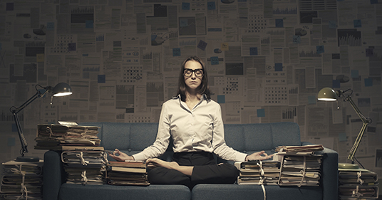 businesswoman practicing mindful breathing to reduce stress at work