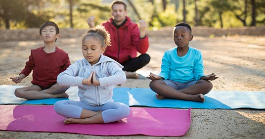coach and children doing meditation for kids in the park