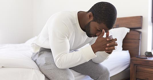 man sitting on bed feeling stressed and full of anxiety