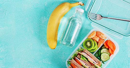 Boîte à lunch scolaire aux habitudes saines avec un sandwich, des légumes, de l'eau et une banane