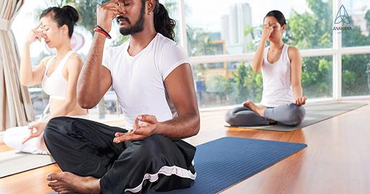Homem e mulher fazendo respiração alternada pelas narinas em um estúdio de ioga