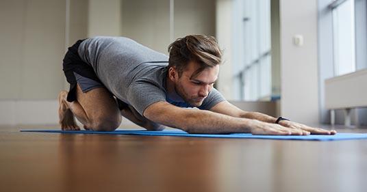 hombre haciendo rehabilitación usando yoga restaurativo para ayudarle