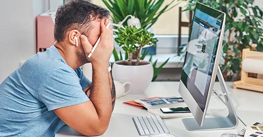 man sitting infront of computer with hands over his face having trouble dealing with stress, needing help with stress management