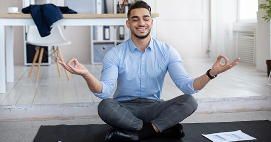 man sitting on the floor performing stress management activities to reduce stress in his daily life