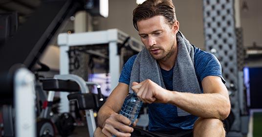 homme avec une bouteille d'eau au gymnase de l'eau potable pour assurer une bonne hydratation saine