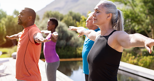 mature group of people performing different breathing techniques outdoor