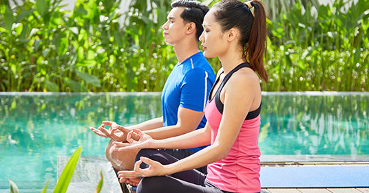 meditating couple performing yoga for beginners